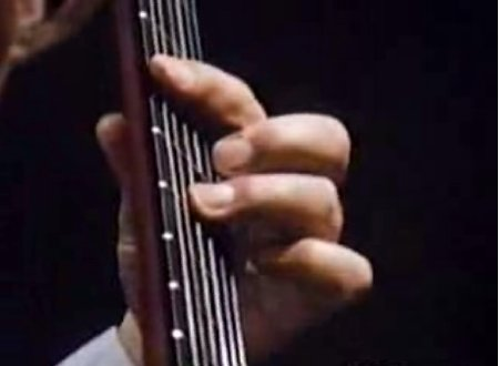 Left hand: Segovia plays a Left hand transversal vibrato (across the neck) with the 3rd finger whilst holding a chord.